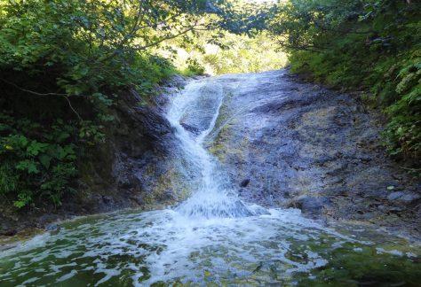 カムイワッカ湯の滝 活火山である知床硫黄山の中腹から涌き出る温泉が川に流れ込み、川全体が流れる温泉のようになっている。